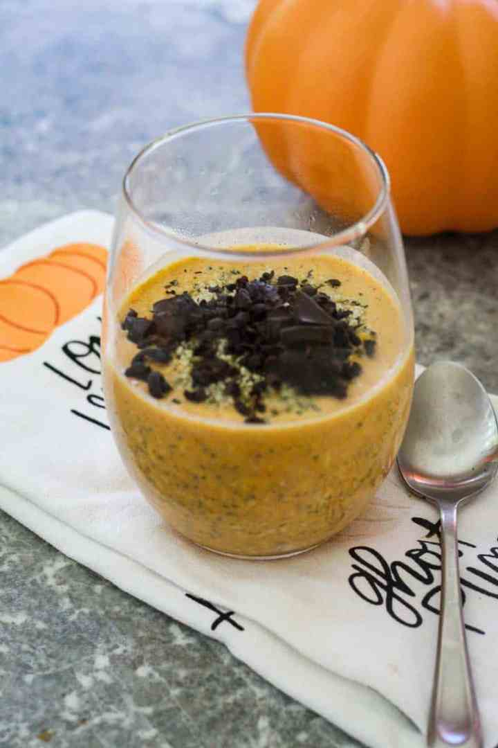 A clear glass, filled halfway with pumpkin chia oatmeal and topped with shaved dark chocolate. Glass is over a pumpkin themed kitchen towel and there's a spoon next to it.