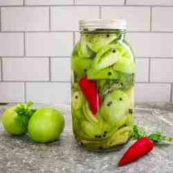 There's a big closed jar with pickled green tomatoes, sliced. You can see a red chili and some peppercorn in the jar too. Next to the jar there's 2 whole green tomatoes, parsley and a red chili.