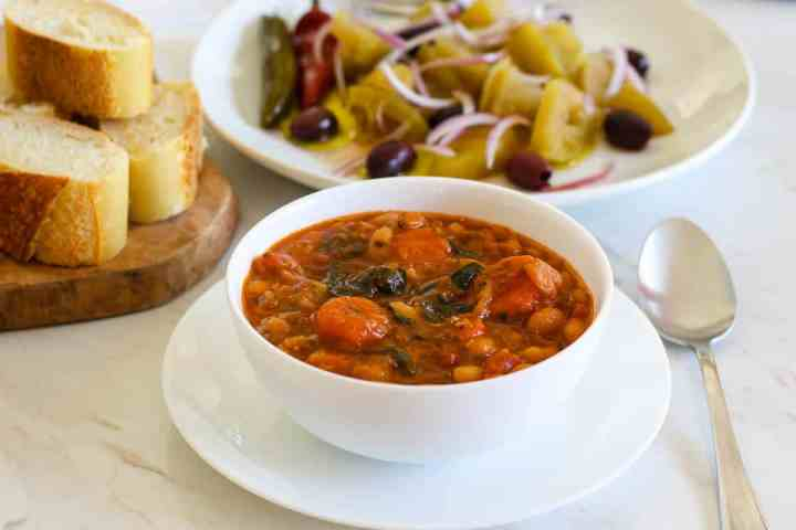 Beans soup served with green tomatoes and bread.