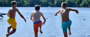 boys jumping off the dock into the lake