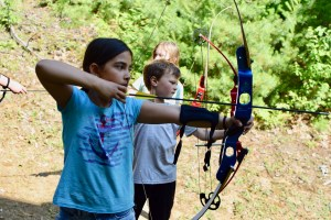 campers taking a bow into the hand and throwing an arrow