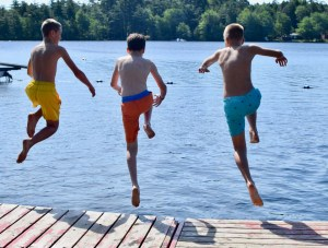 campers jumping off the dock together