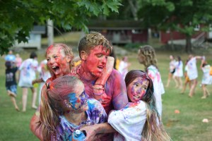 a staffer gets painted by campers