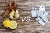 Ginger, lemon, honey and different drugs on wooden background.Alternative remedies and traditional pills to treat colds and flu. Natural medicine vs conventional medicine concept.
