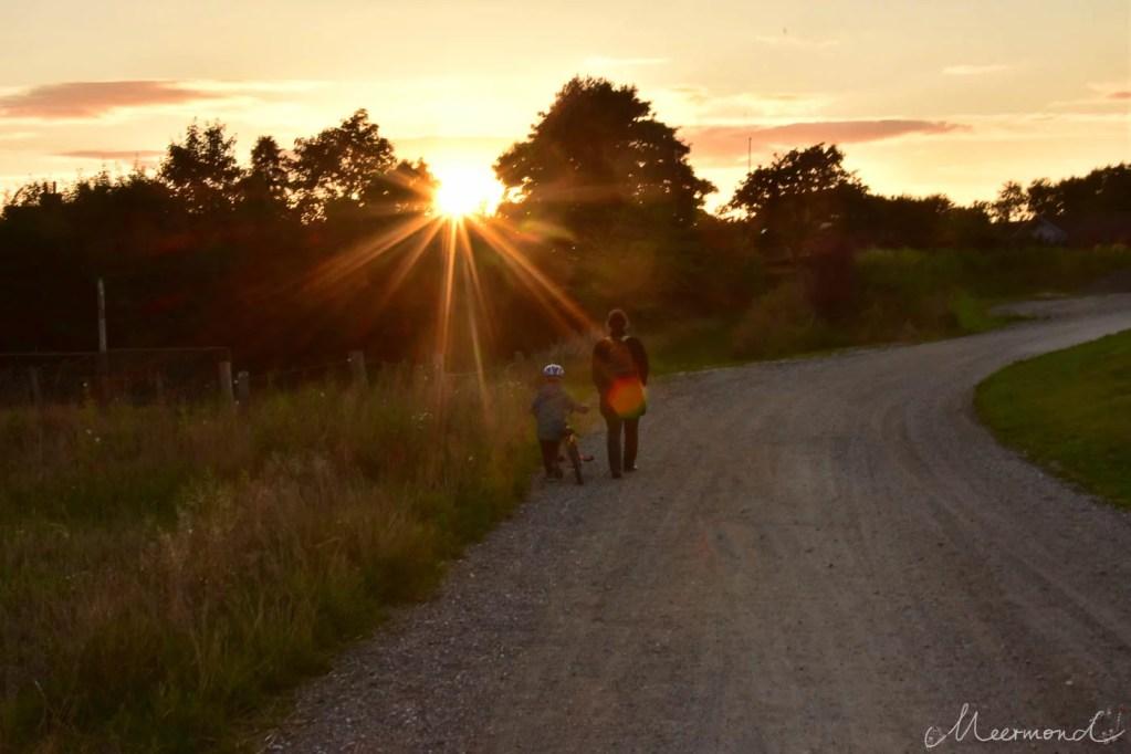 Frau mit Kind spaziert in den Sonnenuntergang