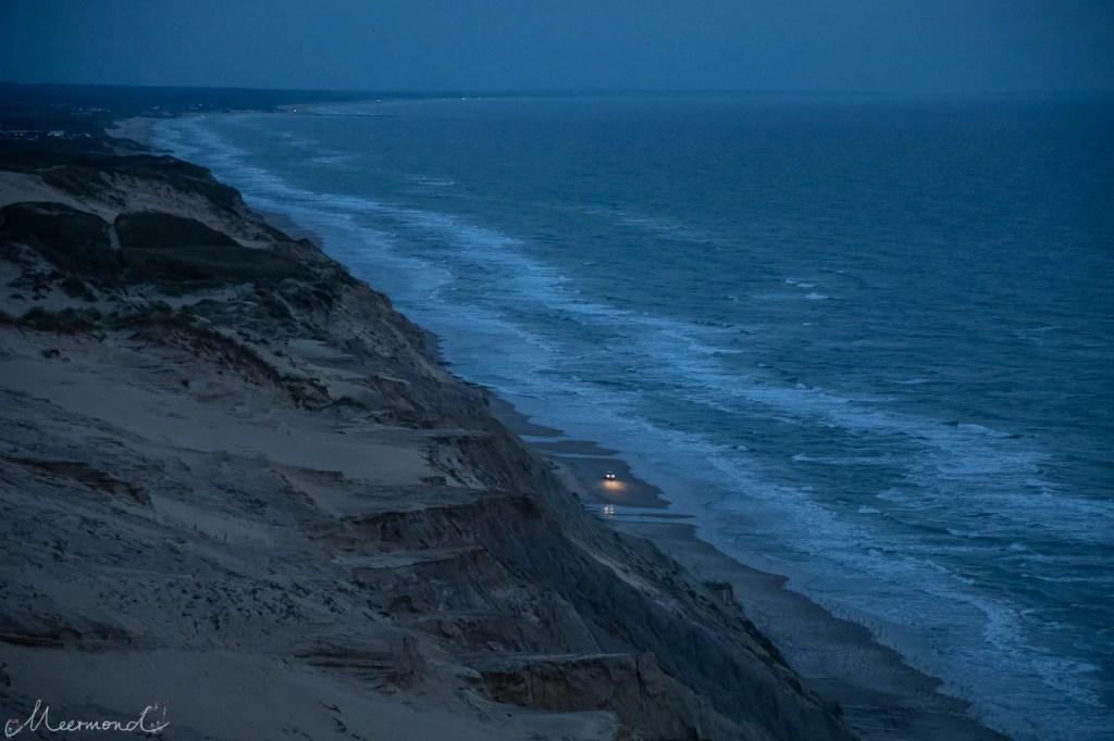 Ein Auto fährt nachts am Strand mit Beleuchtung