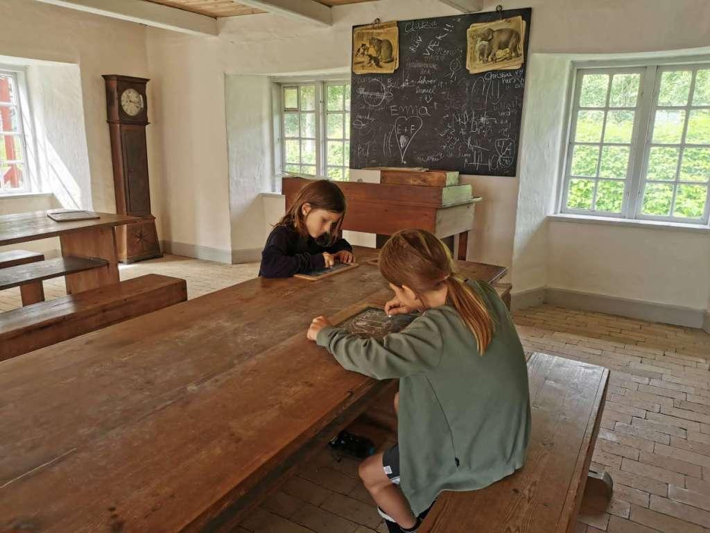 Zwei Kinder sitzen in einer alten Museumsschule an einer Schulbank