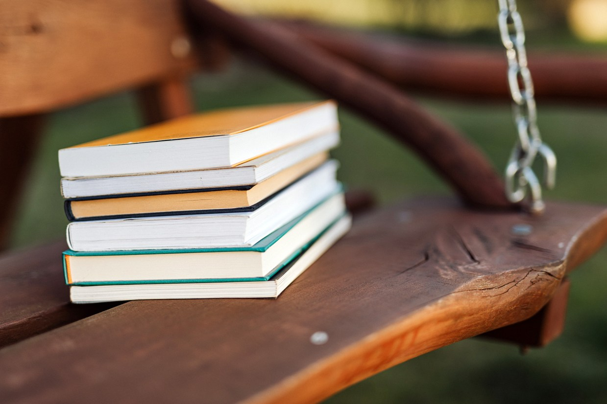 stack of books outside on wooden swing