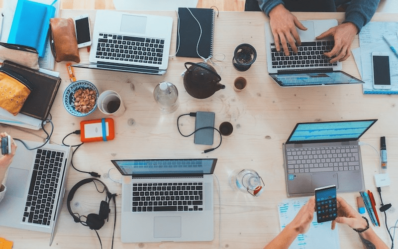 A flat-lay view of on office conference table, with fvive laptops, several other mobile devises, notebooks, beverages, and snacks, with just the hands/arms of three employees visible.