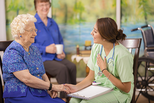 Latin, female doctor visits elderly woman patient in nursing home.