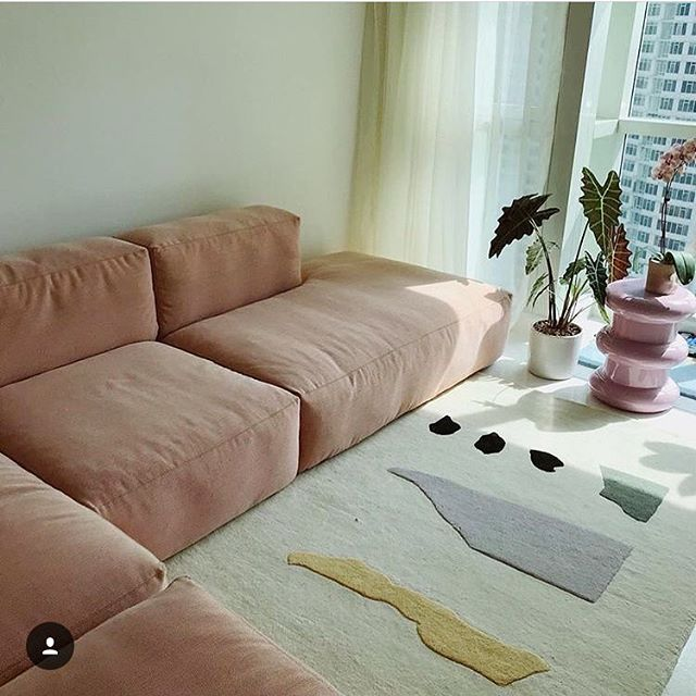 Inspiring Interior: Sunlit minimal pastel living room. ⚪️ Thoughts: 1) This sectional couch is cozy pink perfection. 2) I have the bath mat version of the Talking Rocks rug and am now obsessed with this larger size. 3) That lavender end table and plant vignette is a joyful delight. 📷 @martine via @coldpicnic