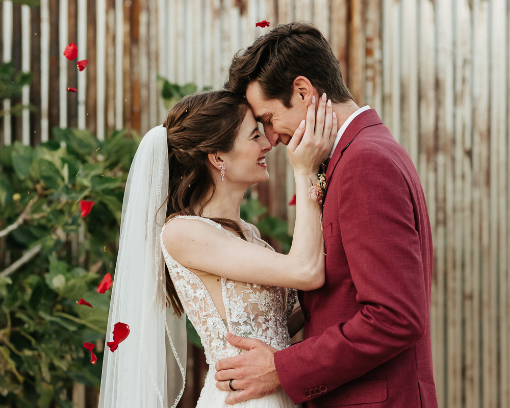 Megan Claire Photography | Arizona Wedding Photographer.  Rustic Glam Backyard Wedding. Groom wearing maroon red suit with bow tie and Bride in beautiful beaded sheer wedding gown with veil