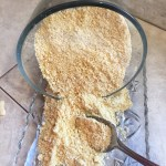 Vegan Parmesan cheese shown in a glass bowl being lifted by a metal spoon