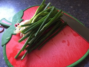 image illustrates the easiest way to store green onions. The green onions are laying side by side on a red cutting board. A large knife is pictured at the end, cutting the green onions.