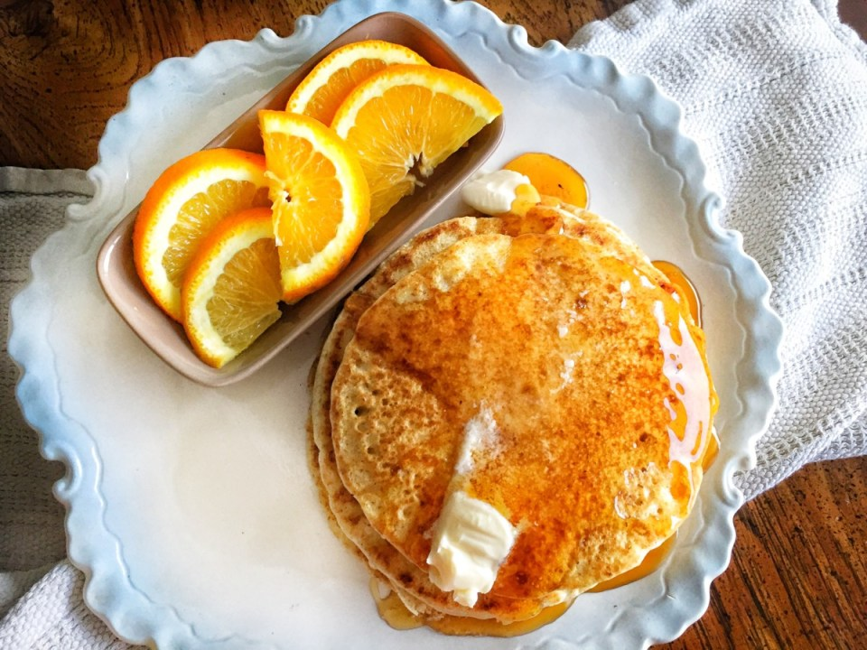 fluffy whole wheat vegan pancakes shown with oranges on the side