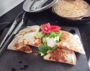 Easy Re-Fried Bean Quesdaillas shown in image cut and topped with cashew sour cream, fresh cilantro and diced tomatoes. The background shows another Easy Re0Fried Bean Quesadilla cooking on a large skillet.