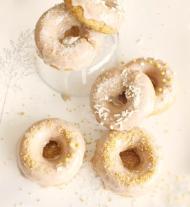 5 Vegan Pumpkin Spiced Doughnuts layed on a white plate with maple glaze