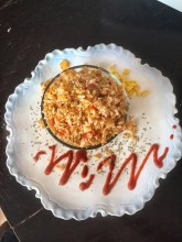 Vegan Mexican Fried Rice shown from above in a clear glass bowl. It is plated with corn and hot sauce swirled around the plate.