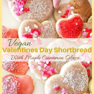 Heart shaped vegan valentines day shortbread cookies shown decorated with white and red sprinkles. A small childs hand is reaching for a cookie.
