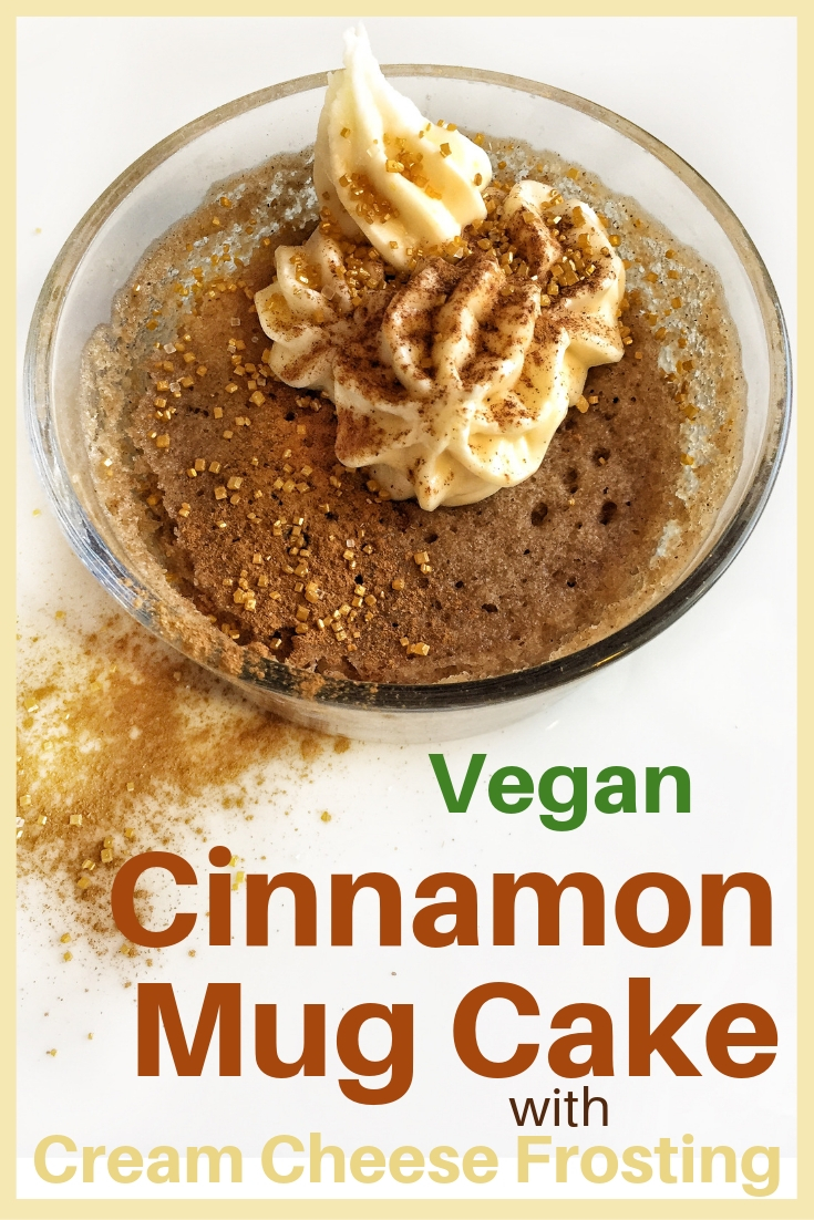 Cinnamon mug cake shown in a glass bowl topped with vegan cream cheese icing and cinnamon