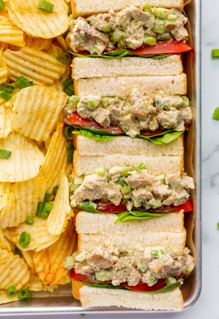 Image shows vegan chicken salad sandwiches packed in a vegan lunch box with a side of ripple chips