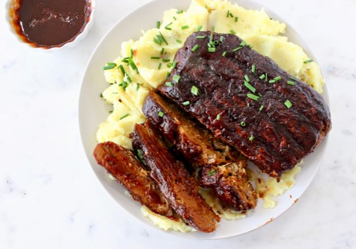 Vegan Ribs shown sliced on a white plate with mashed potatoes and bbq sauce.