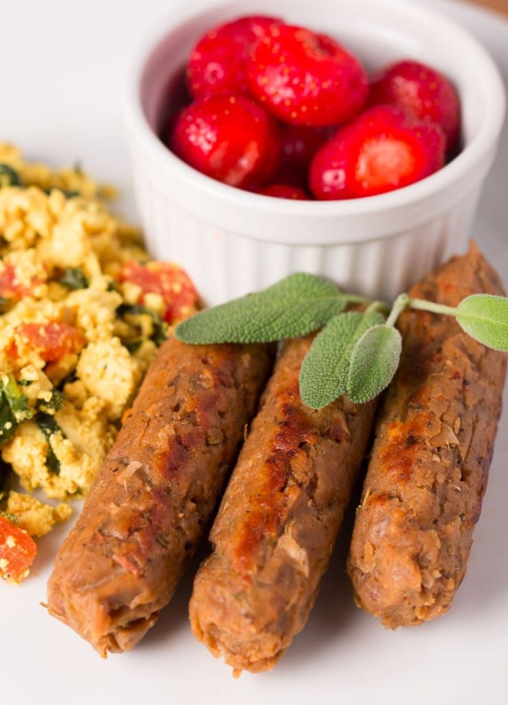 three seitan breakfast vegan sausage links shown on a white plate with fresh sage on top.
