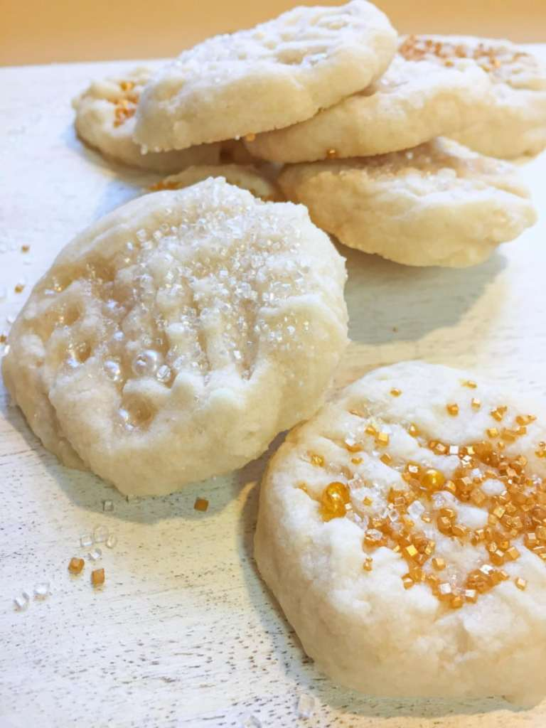Classic vegan Melt in your mouth shortbread on a white plate, topped with gold and silver sprinkles