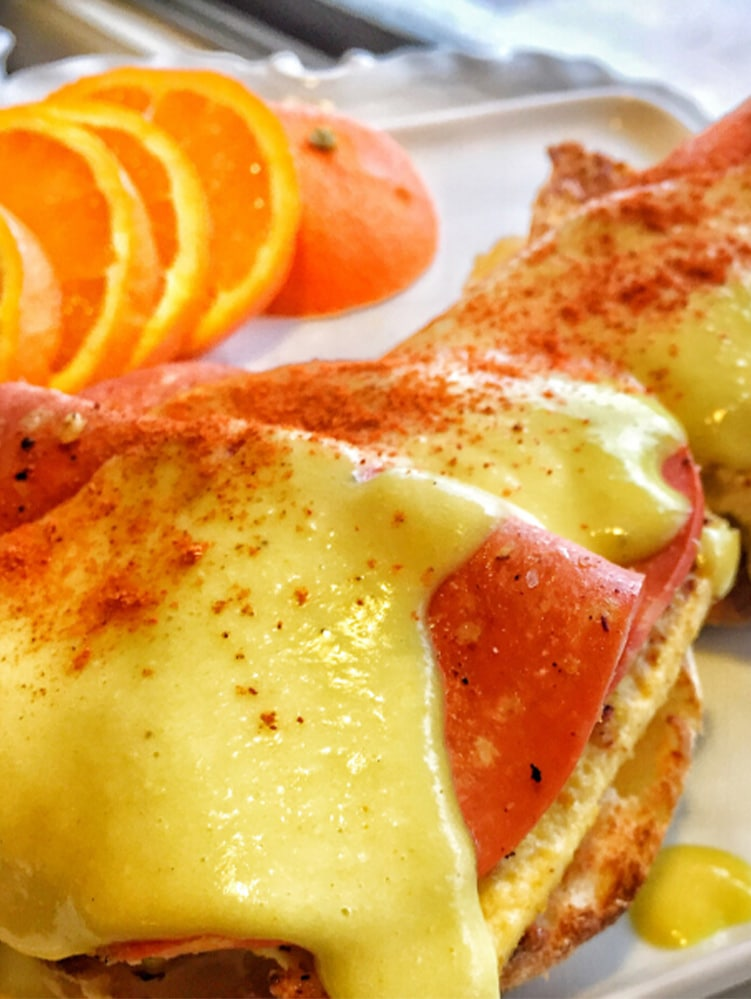 One Vegan eggs benedict smothered in vegan hollandaise sauce. Sliced oranges are pictured on the plate.