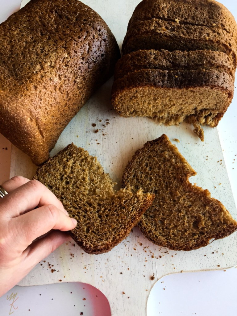 oil free whole wheat vegan bread shown with a piece being picked up.