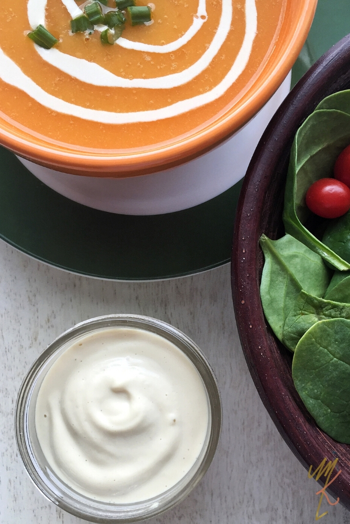 A side of blended cashew cream in a glass jar beside dairy free butternut squash soup