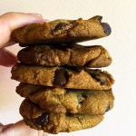 5 crispy vegan chocolate chip cookies stacked on top of eachother against a white background