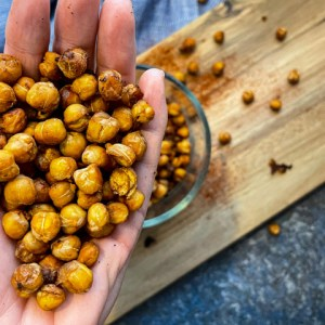 Crispy BBQ Chickpeas in a hand with a bowl of chickpeas below
