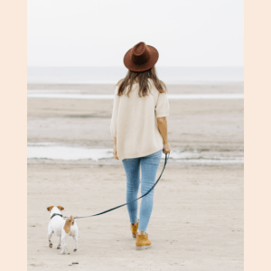 A woman walks her dog along the beach, struggling to stay vegan.