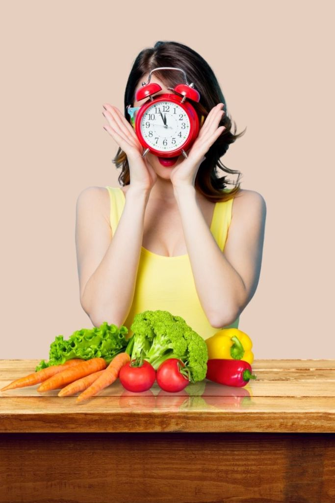 A woman holds a clock in front of her face as she stands in front of a table full of vegetables showing if shes not losing weight as a vegan it could be because shes eating at the wrong times
