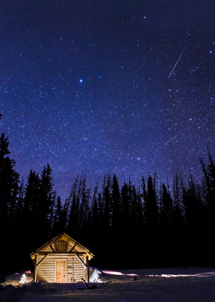 shooting stars over snow survey cabin, in snowy range mountains, Medicine Bow National Forest, Wyoming.