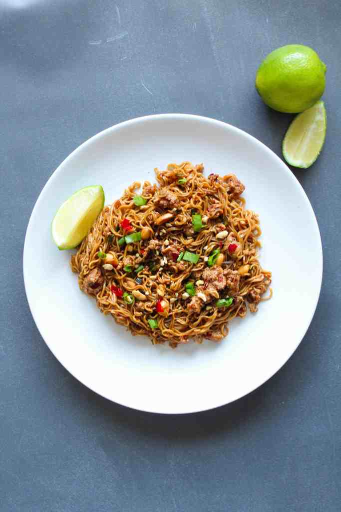 Thai Chicken Noodles on a plate with a lime wedge next to it