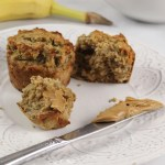 Healthy Peanut Butter Banana Muffins on a plate with a knife, next to a banana and strawberries