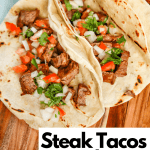 Steak Tacos with Pico de gallo as a topping. Tacos are on wooden serving platter surrounded by pico and limes.