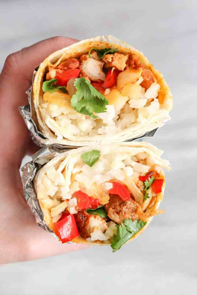 Chicken Burrito with Cauliflower Rice cut in half stacked on top of each other