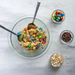 Edible Monster Cookie Dough for Two in a bowl with two spoons , surrounded by toppings