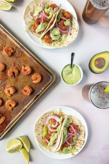 Easy Shrimp Tacos on a Sheet Pan next to tacos on a plate and a small bowl of avocado cream sauce