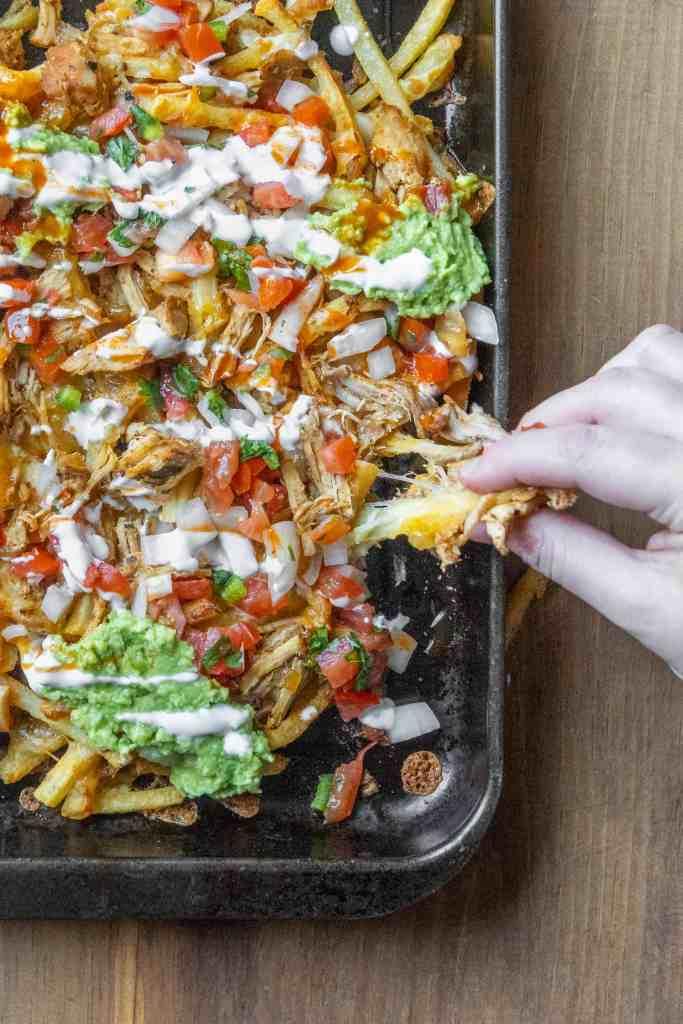Carnitas fries on a sheet pan.