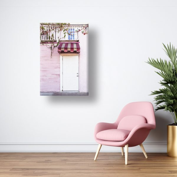 A canvas print hangin on a wall next to a reading chair and plant.