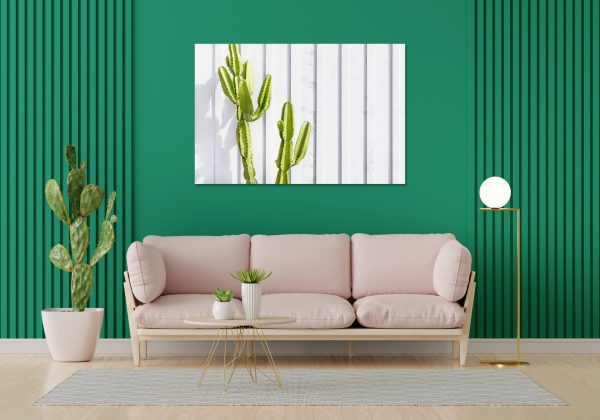 Canvas print of a cactus hanging on a wall over a couch.