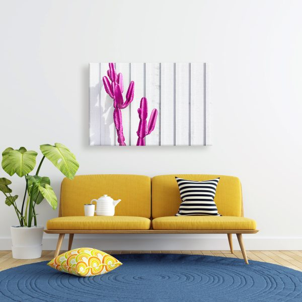 Canvas print of a pink cactus hanging on a wall over a couch.