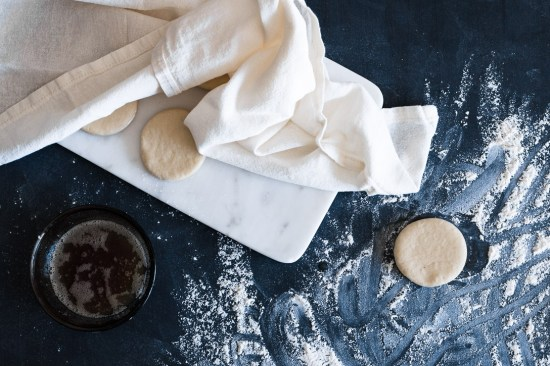 A cut circle of dough on a floured surface next to other dough circles on a marble board partially covered with cloth.