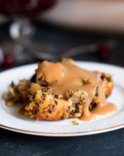 Close up side view of Cornbread and Cranberry Vegetarian Stuffing covered in Vegetarian Mushroom Gravy on a plate.