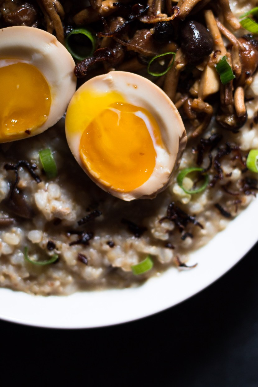 Close up overhead shot of runny ramen egg yolk on top of stir fried mushrooms and congee
