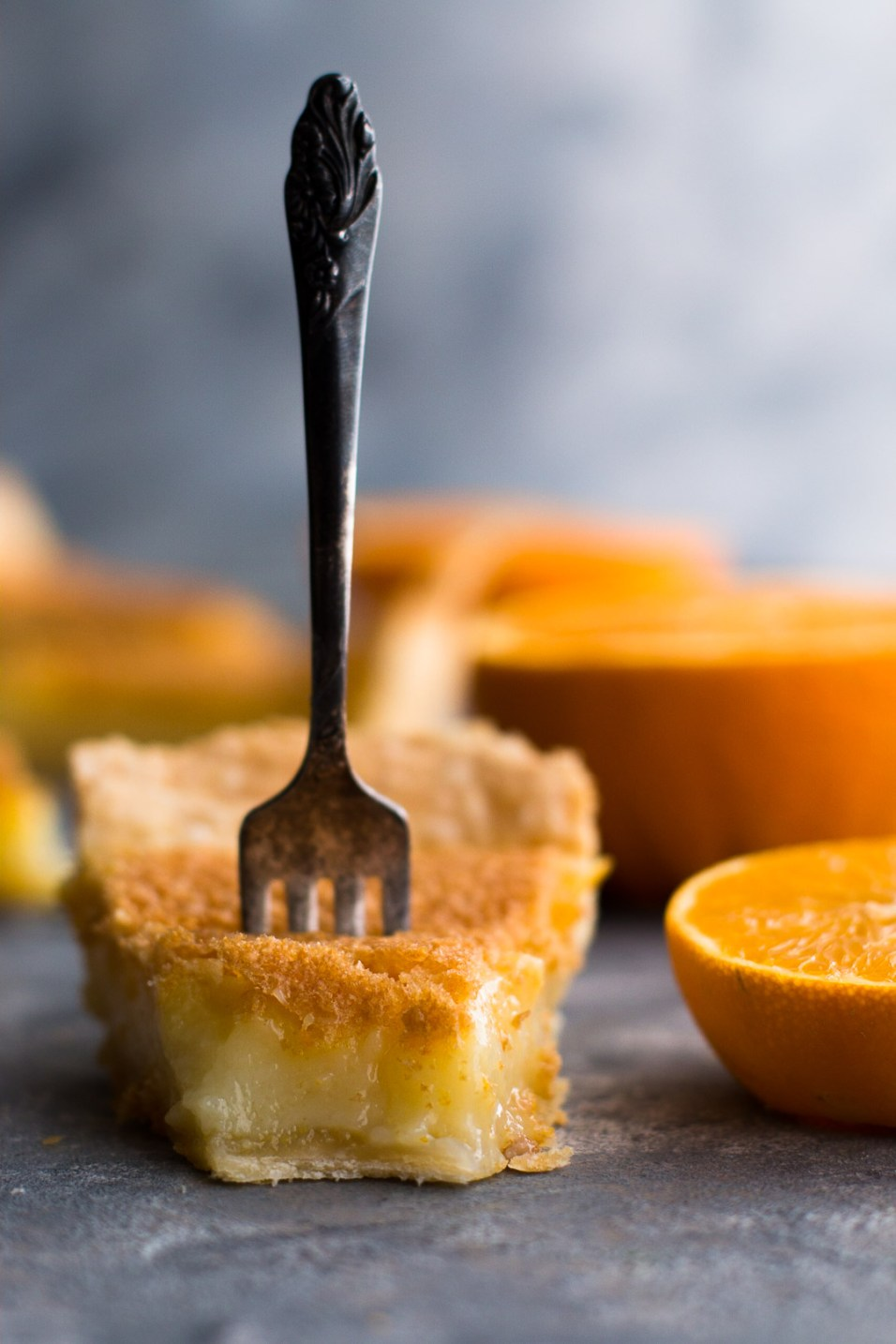 Vertical side shot of a slice of orange chess pie with the tip gone and a fork stuck in it standing up vertically.